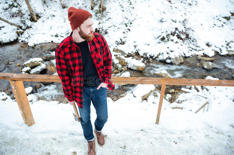 Man with axe standing and looking on small mountain river stock photos