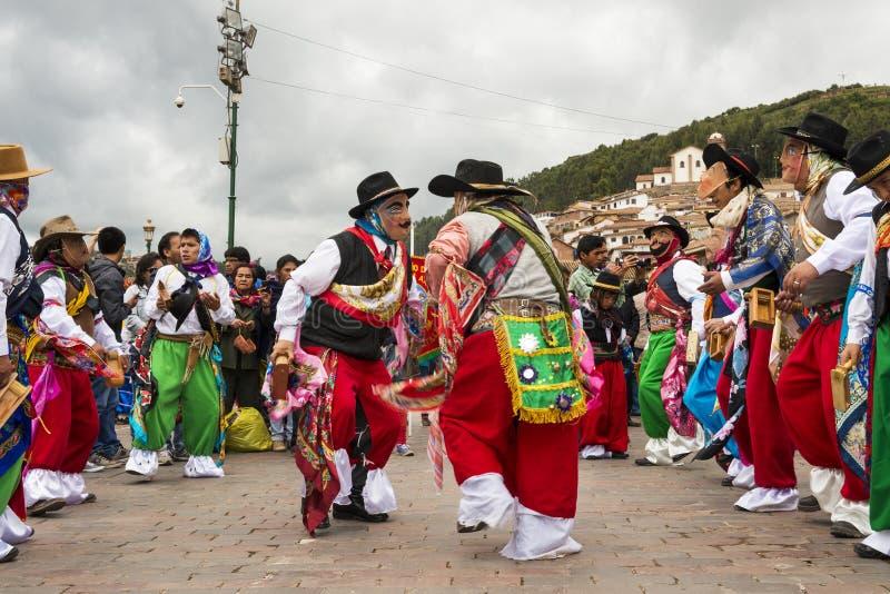 Man bärande traditionella kläder och maskeringar som framme dansar Huayliaen i juldagen av den Cuzco domkyrkan i Cuzco, Peru arkivbilder