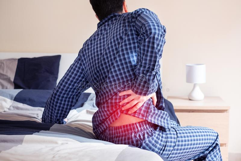 Man with back pain in bed feeling pain stock photos
