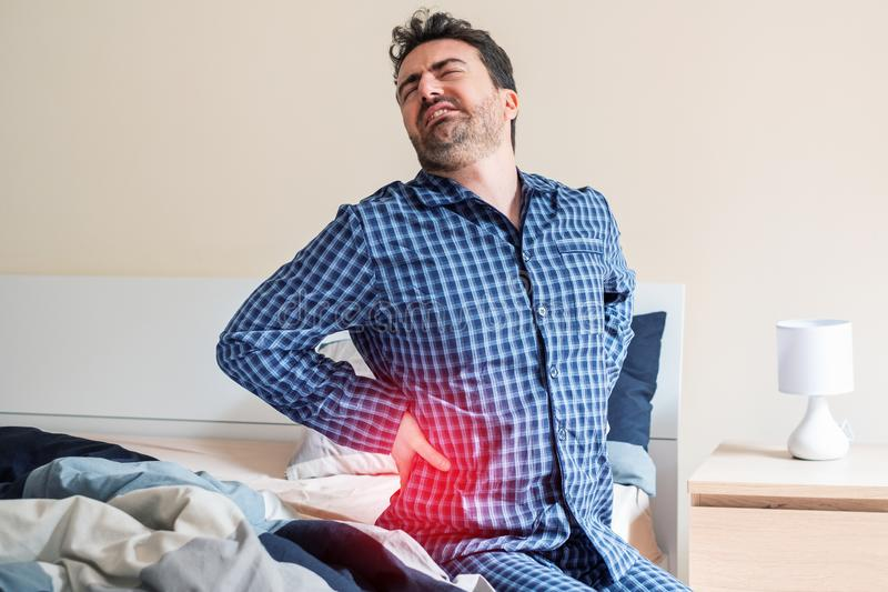 Man with back pain in bed feeling pain stock photography