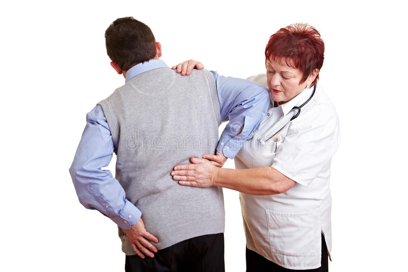 Man with back problems at doctor. Man with back problems seeing a female doctor royalty free stock photos