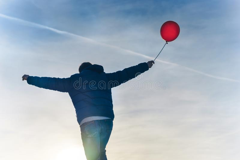 Man from the back with a red balloon in hand against the blue sky on frosty day royalty free stock images