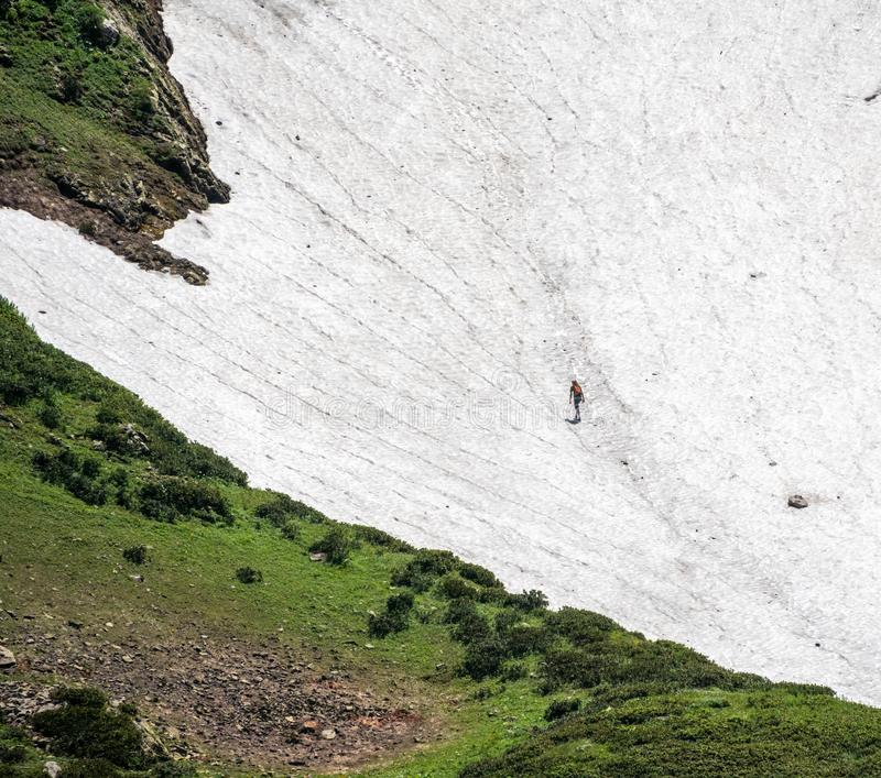 A man with a backpack climbs the snowy slope of the mountain at summer stock photos