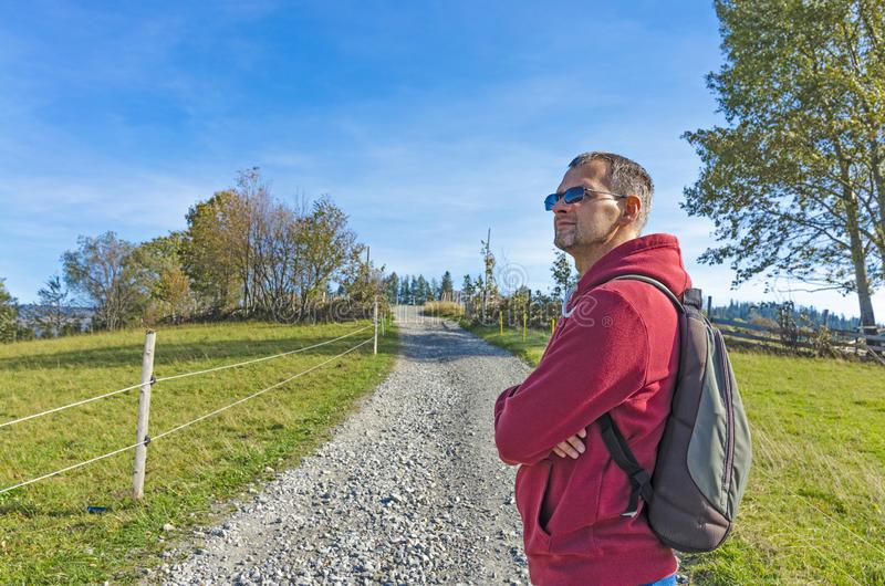 A tourist with a backpack on the country road stock photo