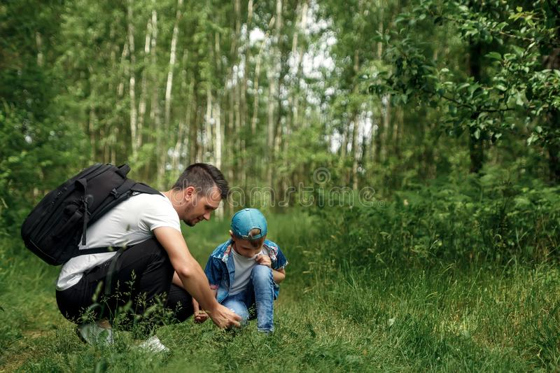 A man with a backpack, a father and his son on a hike, walking during walks in the woods. Family life, pastime with the family, stock images