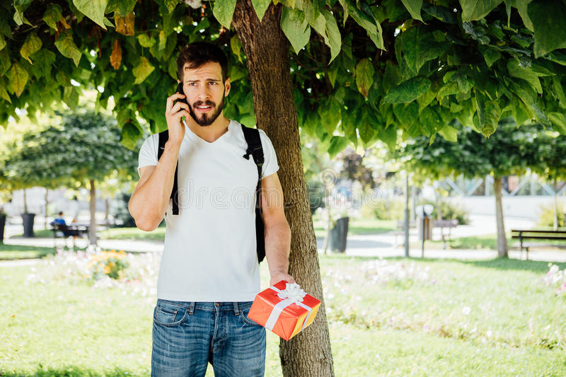 Man with backpack and a gift next to a tree stock photography