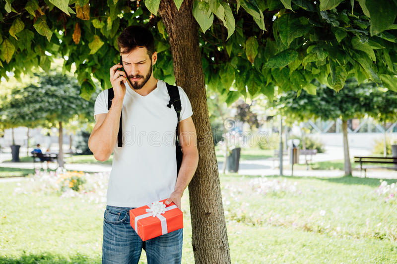Man with backpack and a gift next to a tree stock photos
