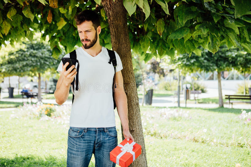 Man with backpack and a gift next to a tree stock photo