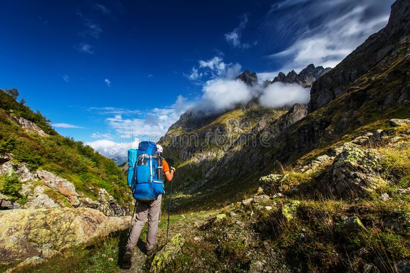 Man with backpack hiking in Caucasus mountains in Georgia stock images