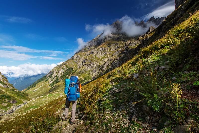 Man with backpack hiking in Caucasus mountains in Georgia stock photos