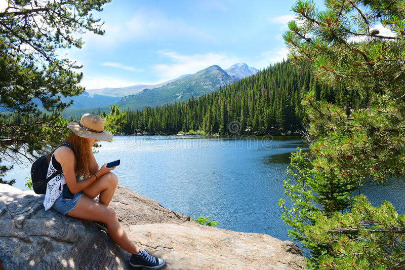 Girl with backpack hiking in mountains on a summer vacation trip. stock image
