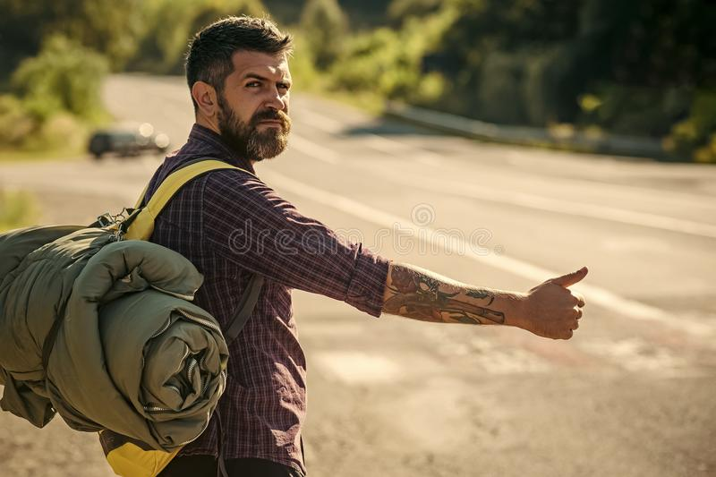 Man with backpack hitchhiking on road. Hipster hiker show thumbs up hand gesture on sunny day. Tourist traveler travel auto stop. Summer vacation concept stock image