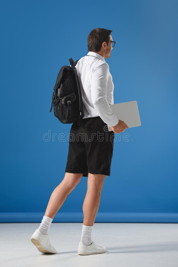 Man with backpack holding laptop and walking. On blue royalty free stock images