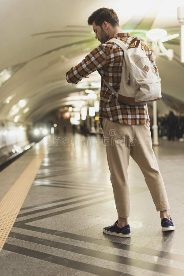 man with backpack looking at wristwatch at subway stock photos