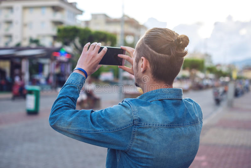 Man backpack makes a photo on your smartphone on a city street stock photography