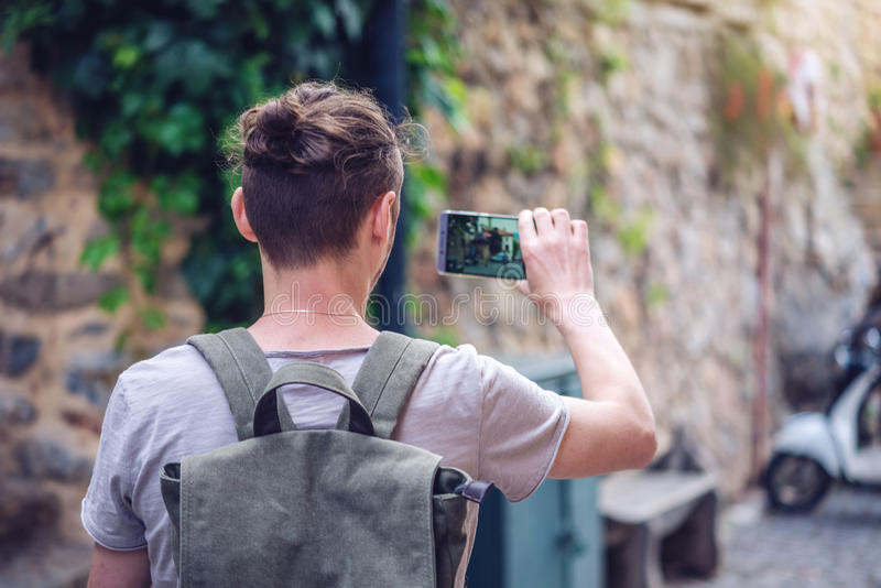 Man backpack makes a photo on your smartphone on a city street stock photos
