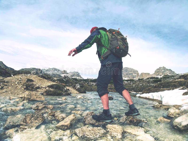Man with backpack moves mountain river royalty free stock images
