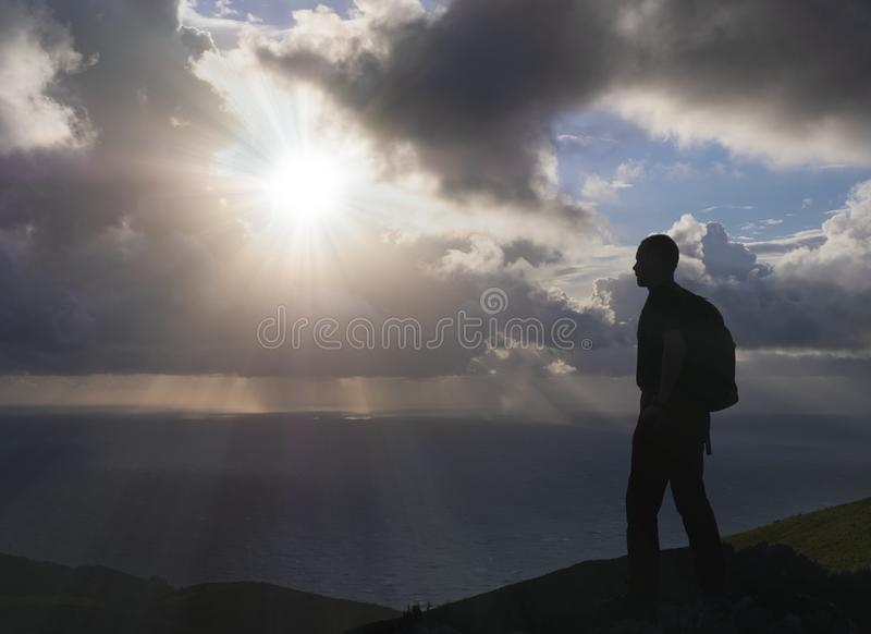 Man with backpack by the sea with sun rays among the clouds stock photos