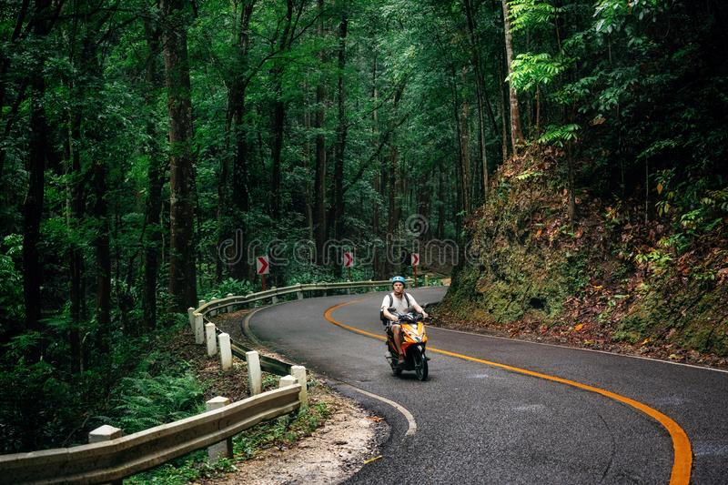 Man with backpack sits in Bohol, Philippines. Man with backpack sits on road through green Bilar Man-Made Forest, Bohol, Philippines stock images