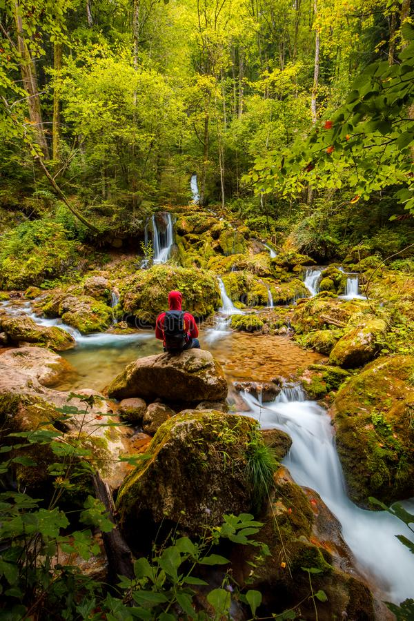 Man with backpack sits on stone at a waterfall in the forest and meditates alone. In austria royalty free stock photos