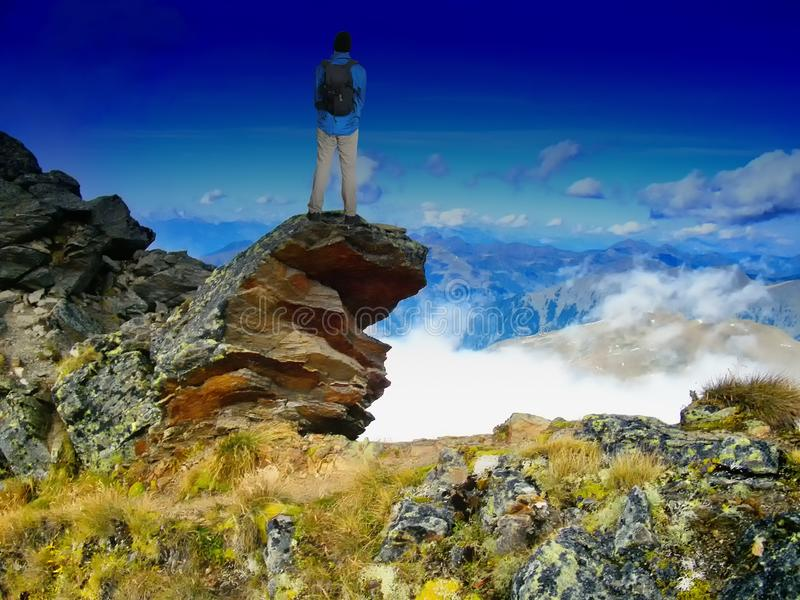 Man with backpack standing on a cliff enjoying a view to valley in scenic mountain landscape stock image