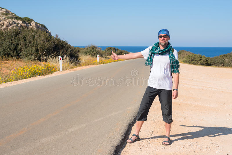 Man with backpack travels hitchhiking. Bearded man with backpack travels hitchhiking, alone on the road, leading to the sea. Sunny day on the coast royalty free stock images