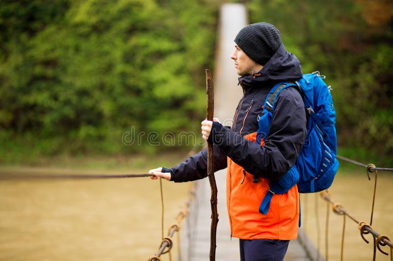 Man with backpack trekking in forest by hinged bridge over river. Cold weathe. Spring hiking. Wooden bridge across the river. Suspension bridge stock photos