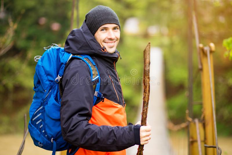 Man with backpack trekking in forest by hinged bridge over river. Cold weathe. Spring hiking. Wooden bridge across the river. Suspension bridge stock image