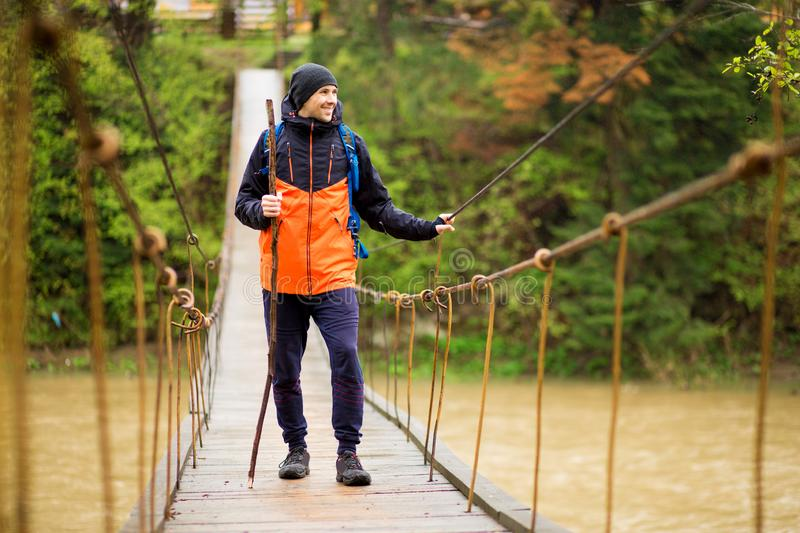 Man with backpack trekking in forest by hinged bridge over river. Cold weathe. Spring hiking. Wooden bridge across the river. Suspension bridge royalty free stock photography
