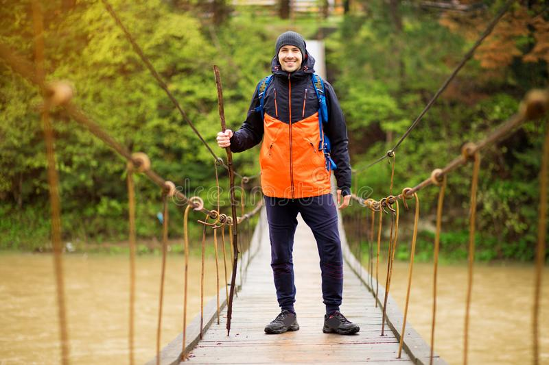 Man with backpack trekking in forest by hinged bridge over river. Cold weathe. Spring hiking. Wooden bridge across the river. Suspension bridge royalty free stock photo