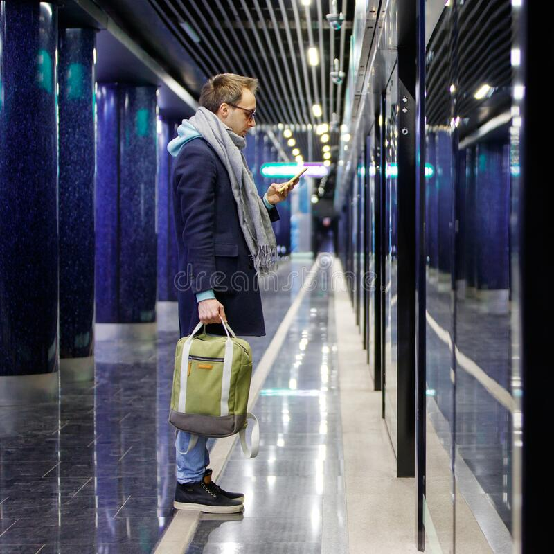 Man with backpack using smartphone, waiting train at subway station platform, holding a cup of coffee. Caucasian young man with backpack using cellphone, waiting stock photos