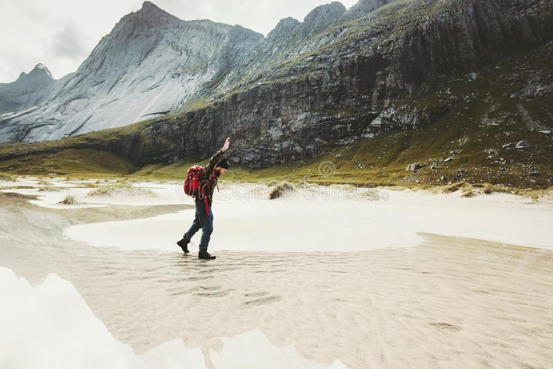 Man with backpack walking alone at sandy beach stock photography