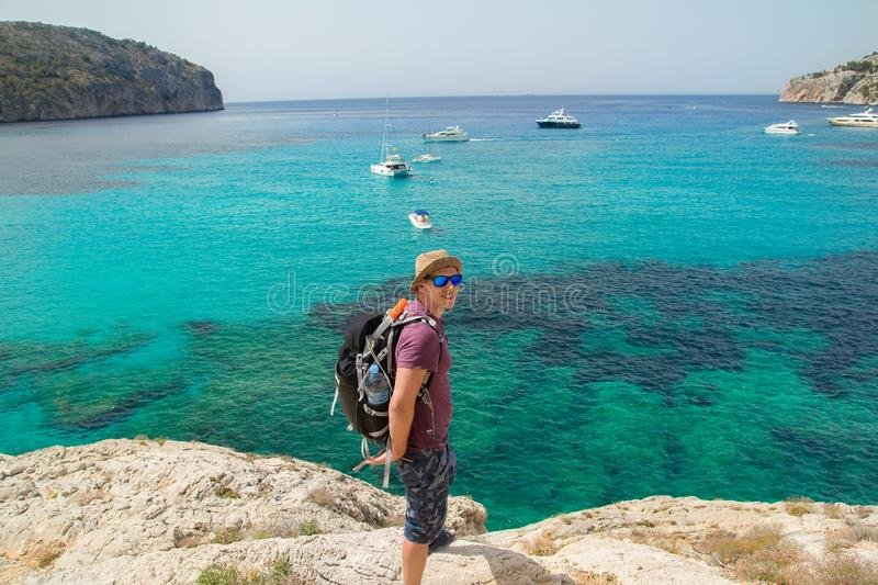Man with backpack walking on cliffs above sea royalty free stock photos