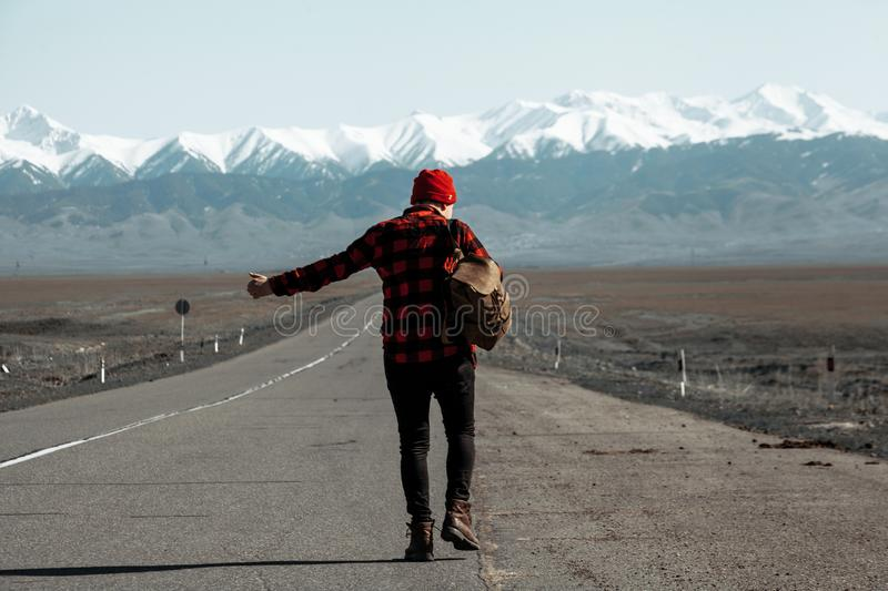 Man with backpack walking down a road while hitchhiking. Man dressed in red shirt and red hat walking down a mountain road while hitchhikking stock photography