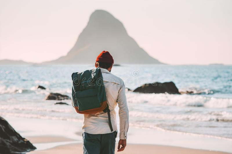 Man with backpack walking on empty beach traveling. Lifestyle vacations in Norway outdoor solitude emotions royalty free stock photos