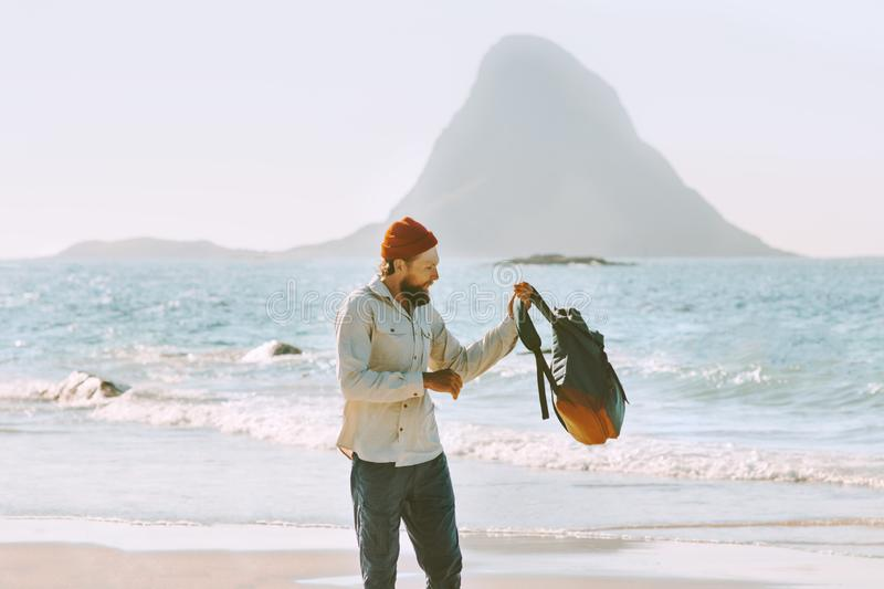 Man with backpack walking on ocean beach stock photos