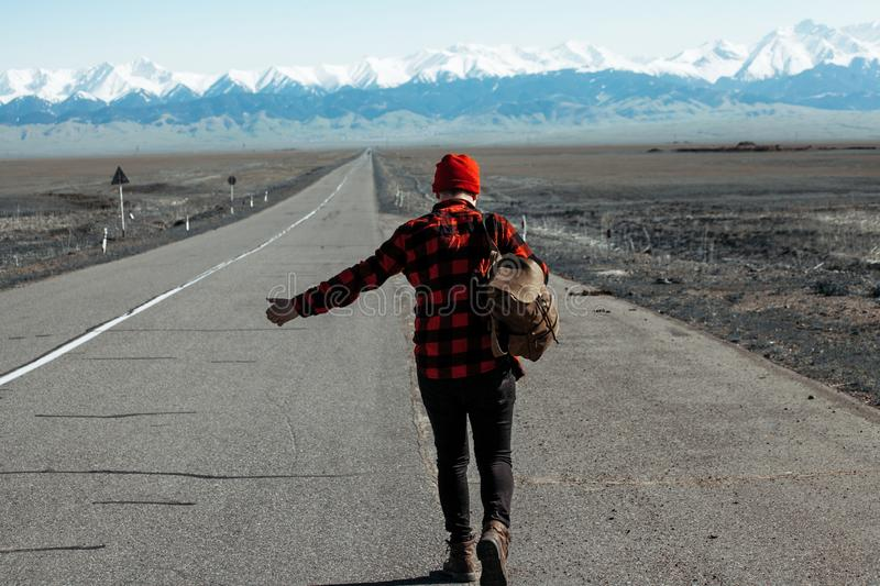 Man with a backpack walks on a mountain road. MAn in red shirt and hat and bacpack waking down in mountain road royalty free stock photo