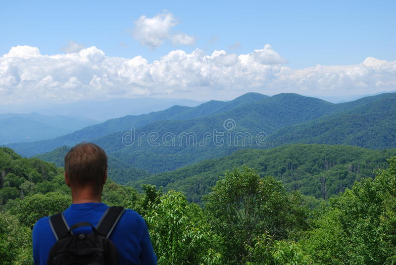 Man with backpack watching on the blue mountains and line of clouds royalty free stock photography