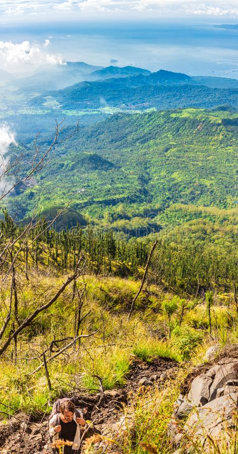 Man backpacker hikes on Agung volcano slope and looks on the astounding landscape. Panoramic vertical view from a high green hill royalty free stock photo