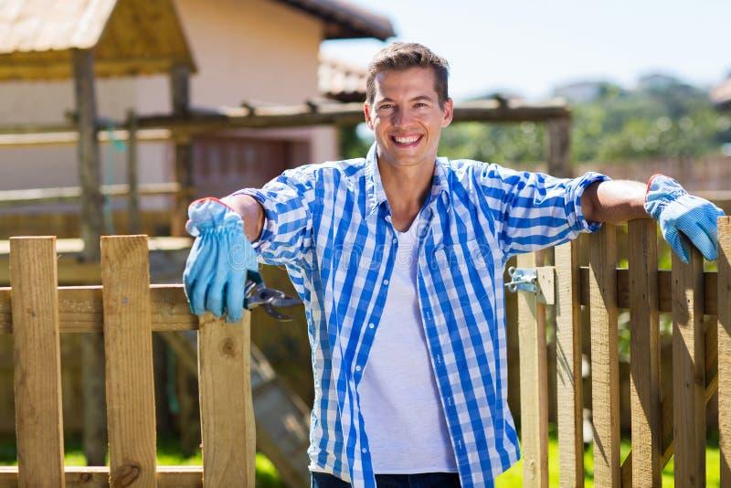 Man backyard gate. Handsome caucasian man holding a garden tool standing by backyard gate royalty free stock photography
