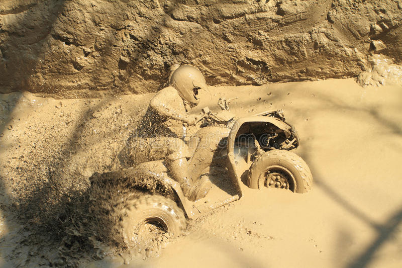 Man badly stuck in mud with his quadbike stock photos