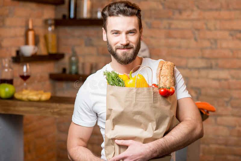 Man with bag full of food. Handsome man holding a paper bag full of healthy food in the kitchen royalty free stock images