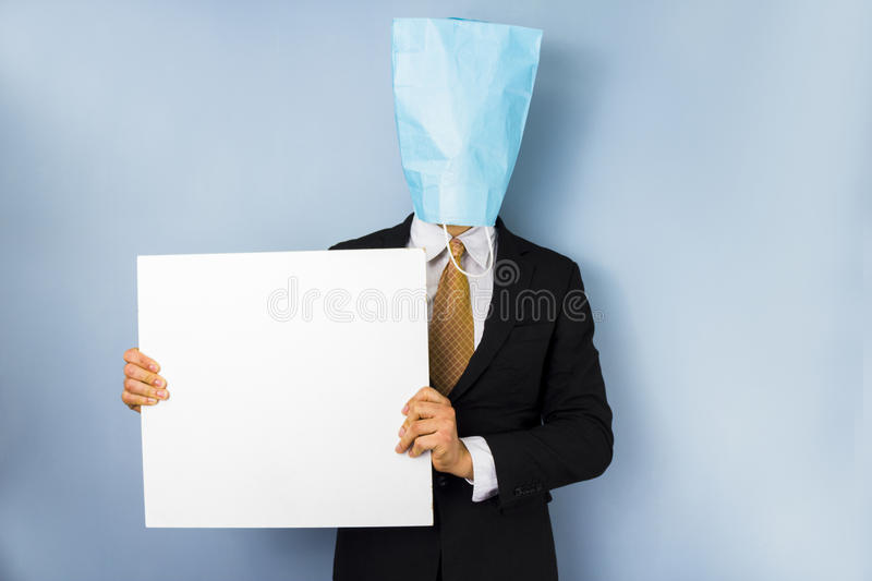 Man with bag over head holding blank sign stock photography