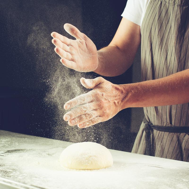 man baker sprinkled flour on roll dough on a wooden board. Process of preparing pizza. Cooking time, cooking concept, selective f stock images