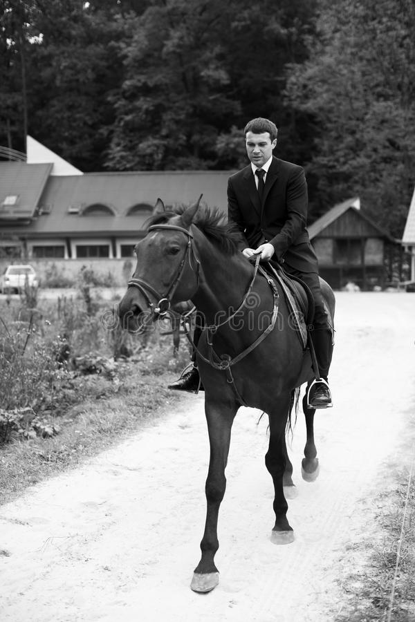 Man in balck suit rides a horse along the road. A royalty free stock photo