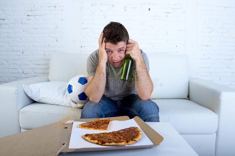Man with ball pizza and beer bottle watching football game on tv covering eyes sad and disappointed for failure or defeat. Young supporter man with ball pizza royalty free stock photos