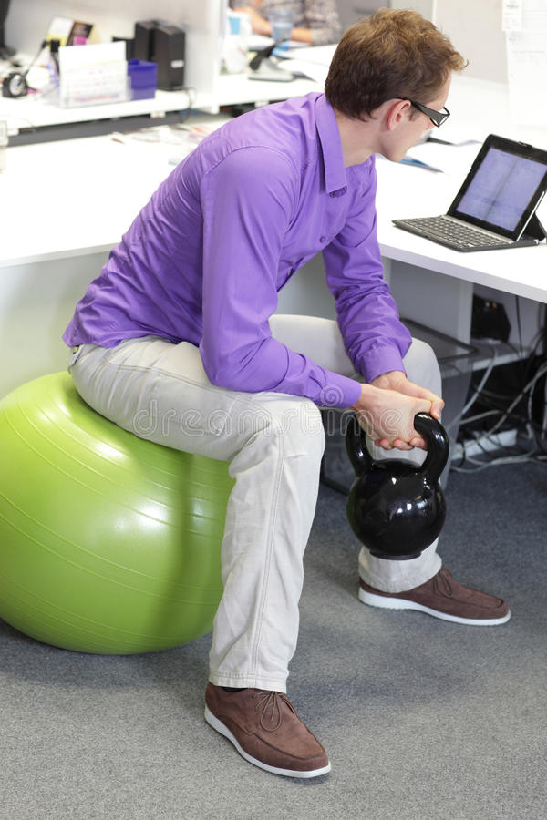 Man on ball working out with kettlebell during offce work stock photography
