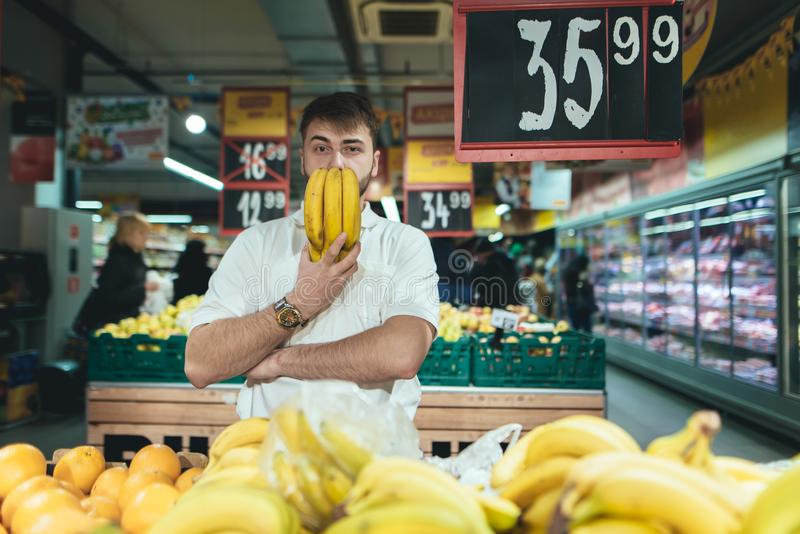 A man with bananas in his hands poses in a supermarket when shopping. The buyer buys the fruit in the store. royalty free stock images