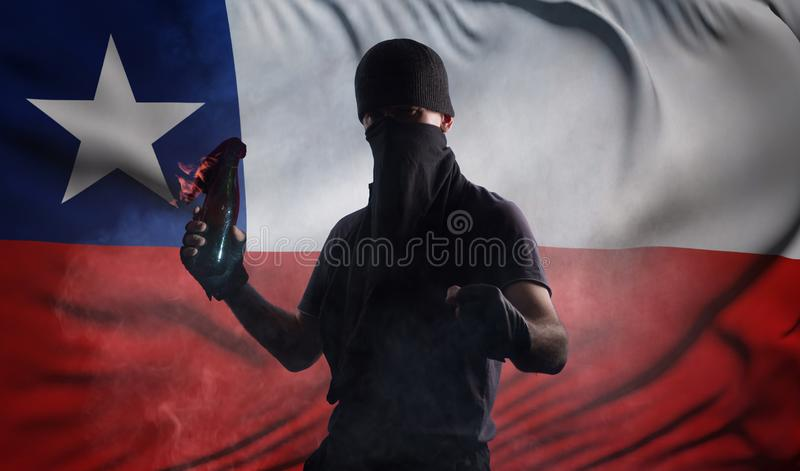 A man with a bandage on his face with a burning bottle in his hands on the background of the flag of Chile stock photography