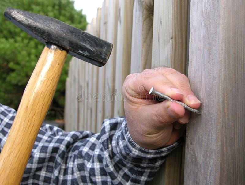 Man Bangs Nail Into A Wooden Wall Royalty Free Stock Photo